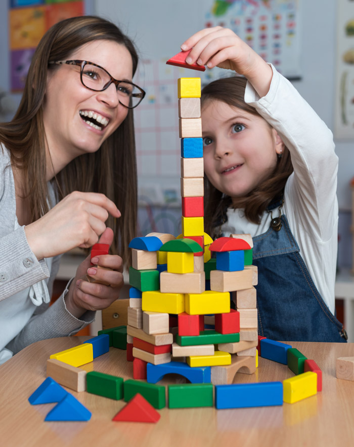 Teacher with student building block tower